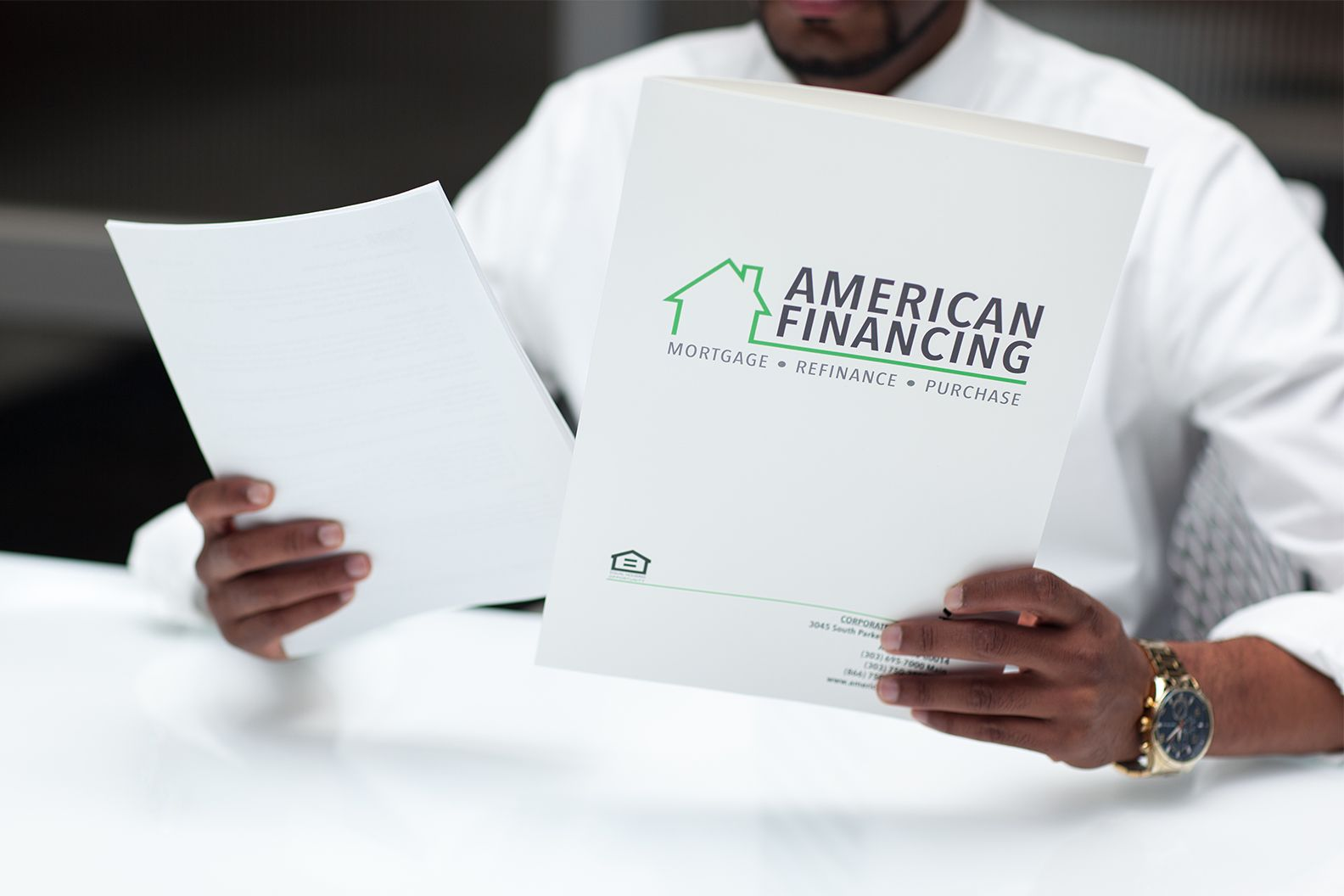 American Financing employee looking at folders with loan documents