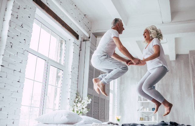 Retired couple jumping on bed