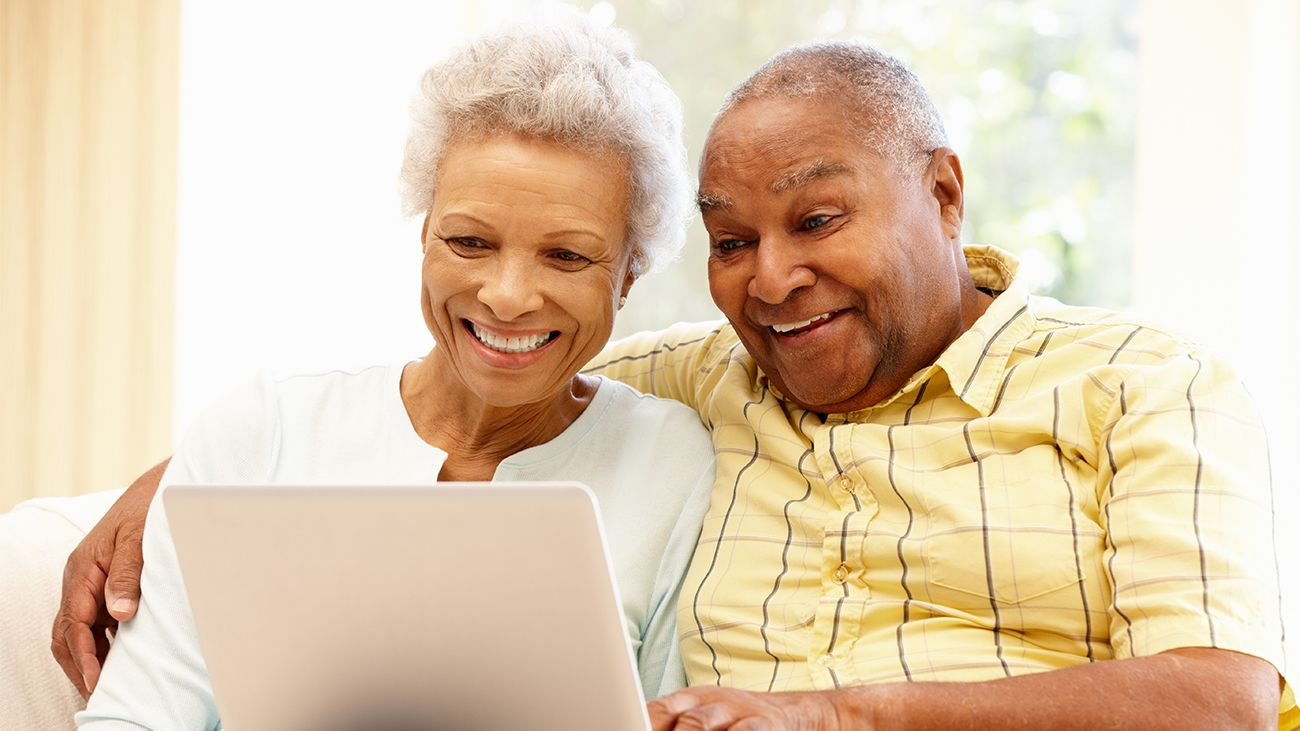 Senior couple researching reverse mortgages on a laptop