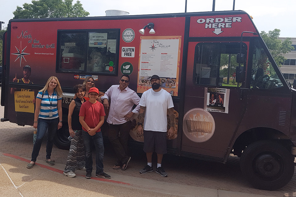 AFC employees standing with a food truck