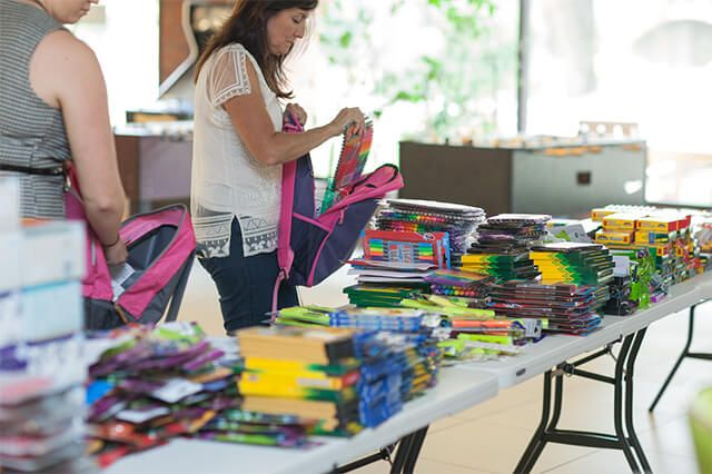 AFC employee donating to There with Care backpack drive