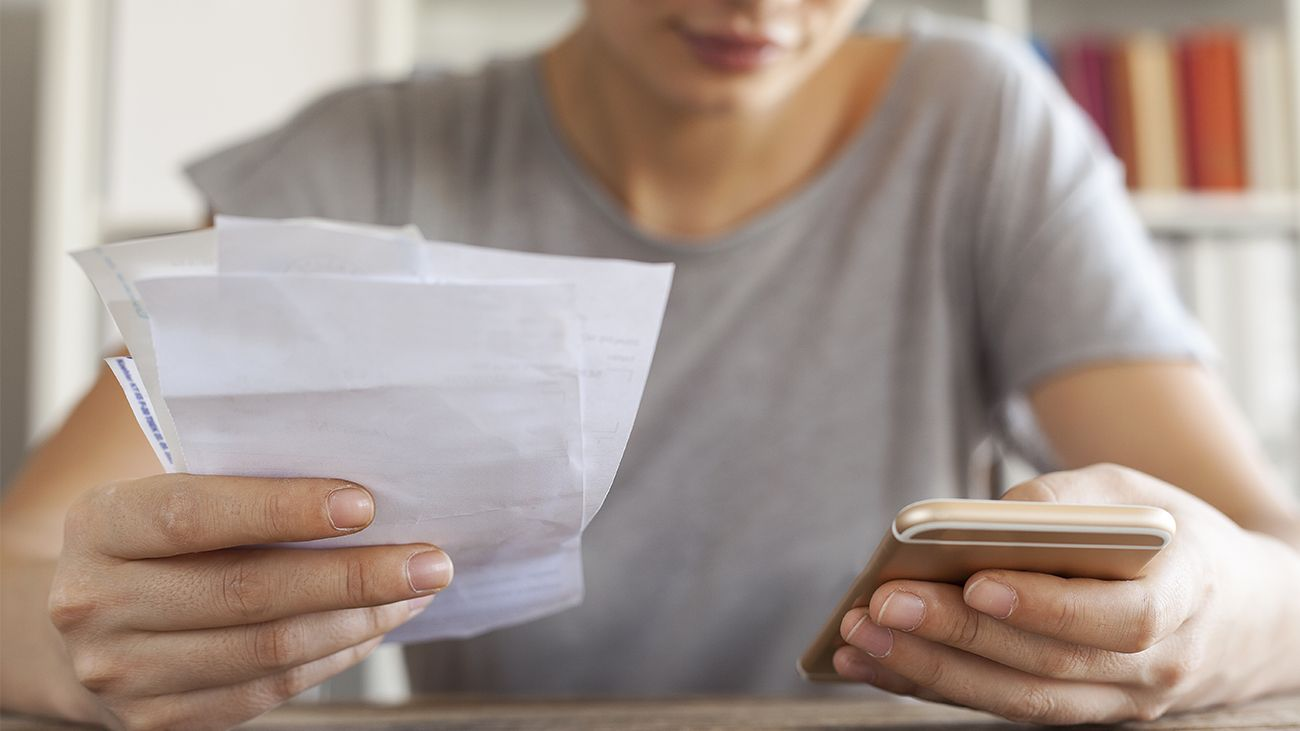 Woman calculating receipts with a phone app