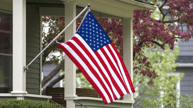 American flag hanging in front of covered porch