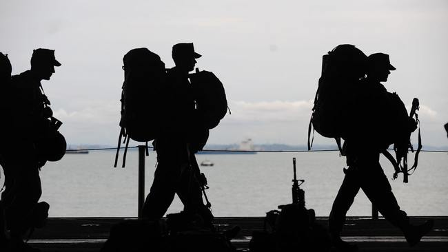 Military men walking near water