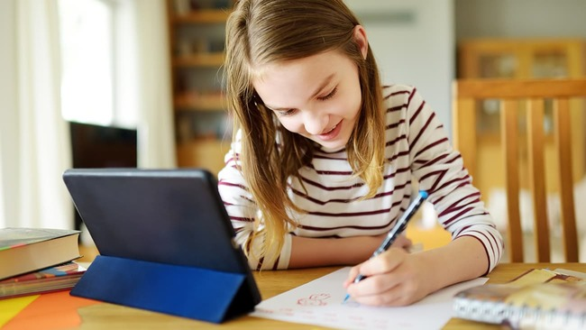 Young girl doing schoolwork at kitchen table