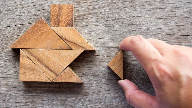Hand placing puzzle pieces in the shape of a home