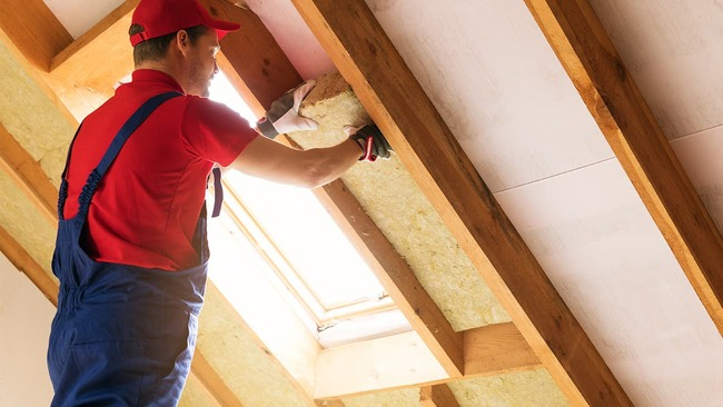 Construction worker adding insulation to attic
