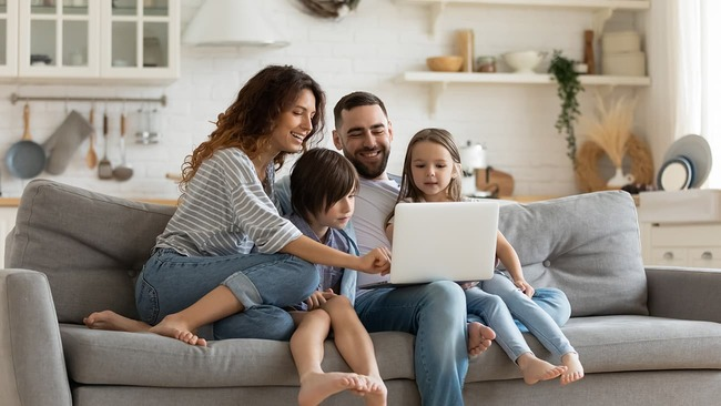 Happy family sitting on couch and looking at laptop