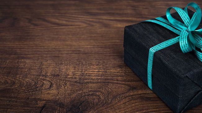 Black gift package with blue bow on wood table