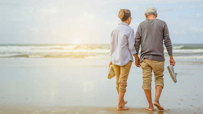 Retired couple holding hands while walking on the beach