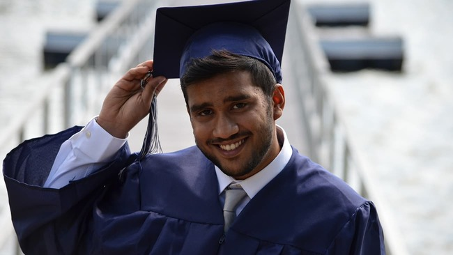 College graduate holding his cap