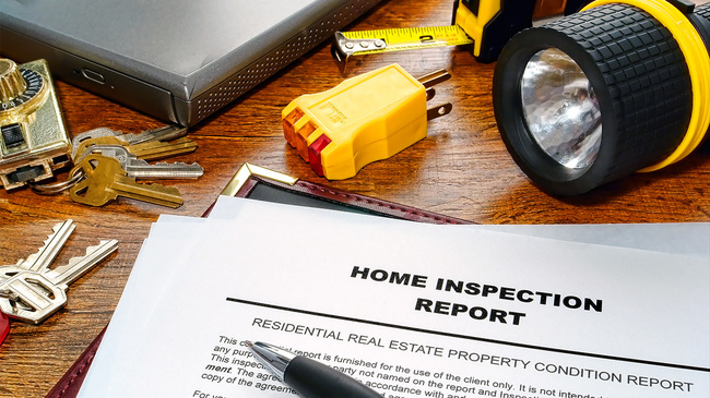 Home inspection report with keys and flashlight