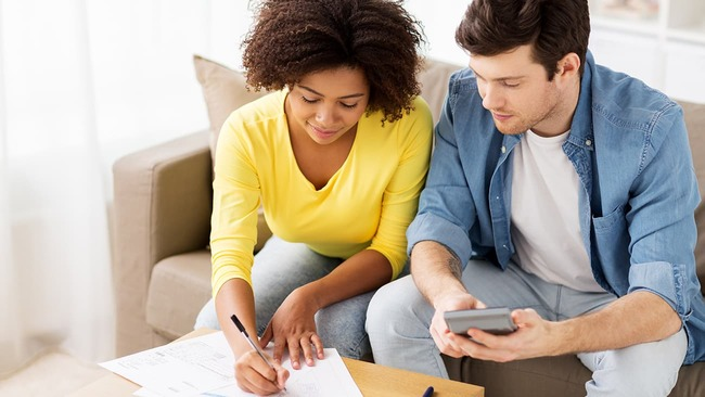 Couple making a budget while sitting on couch