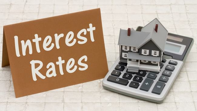 Interest rates sign nest to small house and calculator