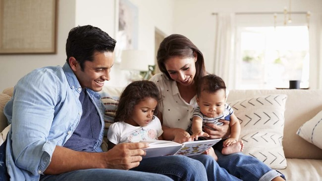 Young family reading a book in living room