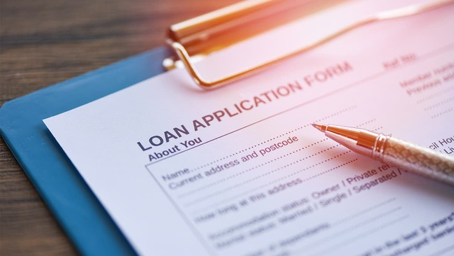 Loan application form and pen on clipboard