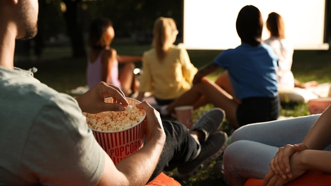 Young people enjoying an outdoor movie night
