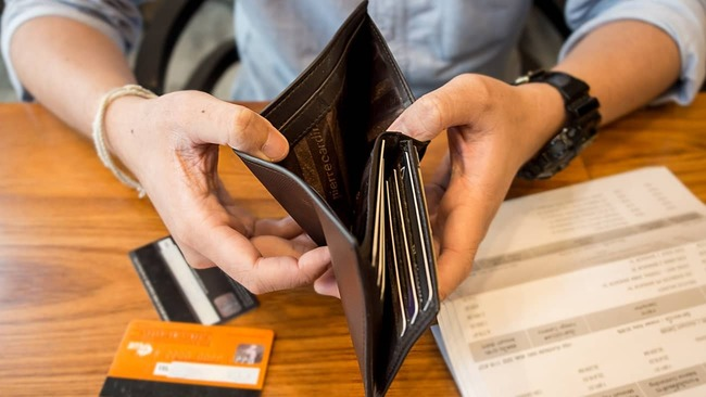 Man looking into wallet for money and credit cards.