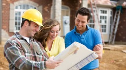 Happy couple reviewing home plans with builder