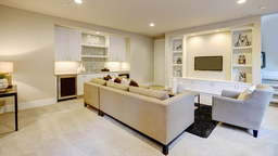Modern basement with gray sectional, mounted TV,  and wet bar