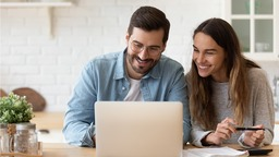 Happy couple looking at laptop in kitchen