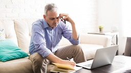 Man on phone in living room with laptop, pen, and paper