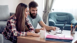 Couple reviewing budget in living room