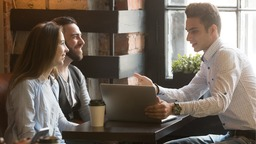 Couple talking with lender at coffee shop