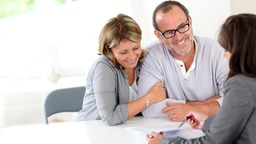 Happy couple meeting with lender